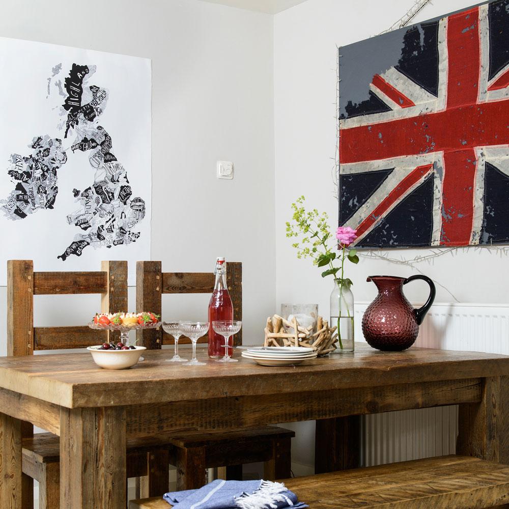 Sala da pranzo tradizionale bianca con set da pranzo in rovere e stampe patriottiche